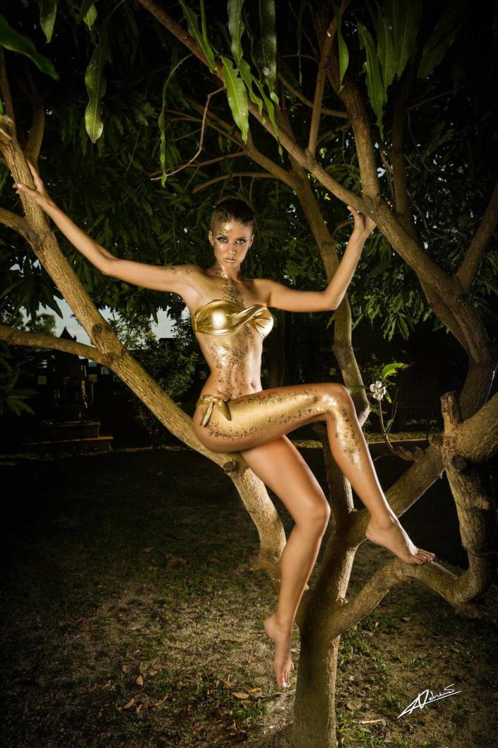 Fantasy photography woman with gold bodypaint on the tree.