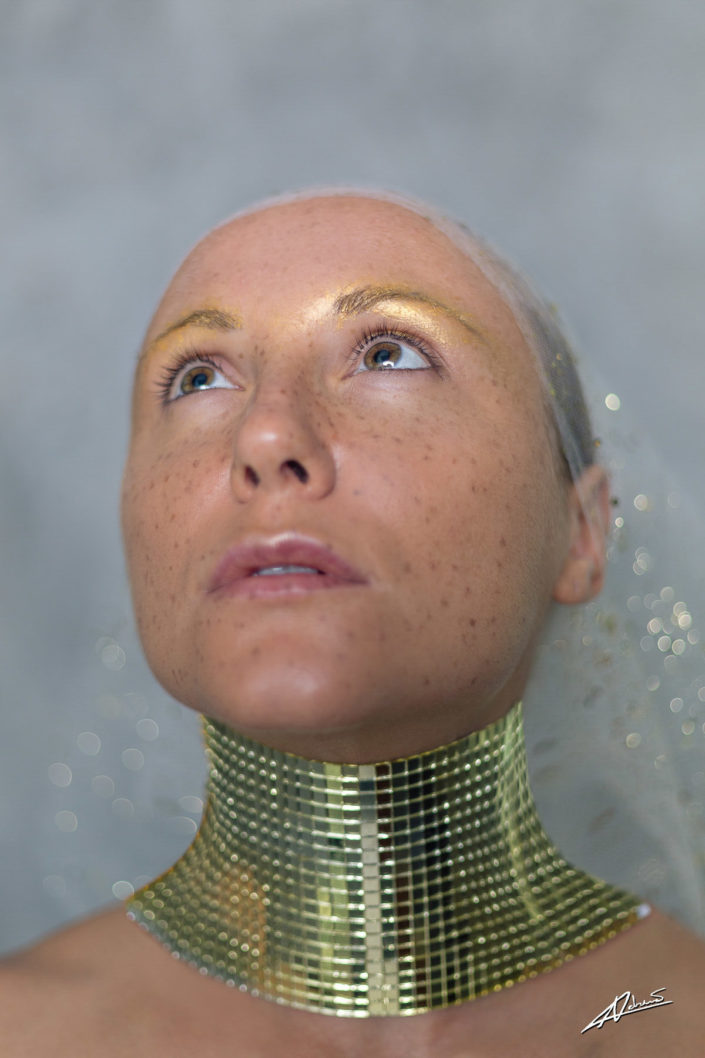 Fantasy photography woman with gold disco ball on her neck.
