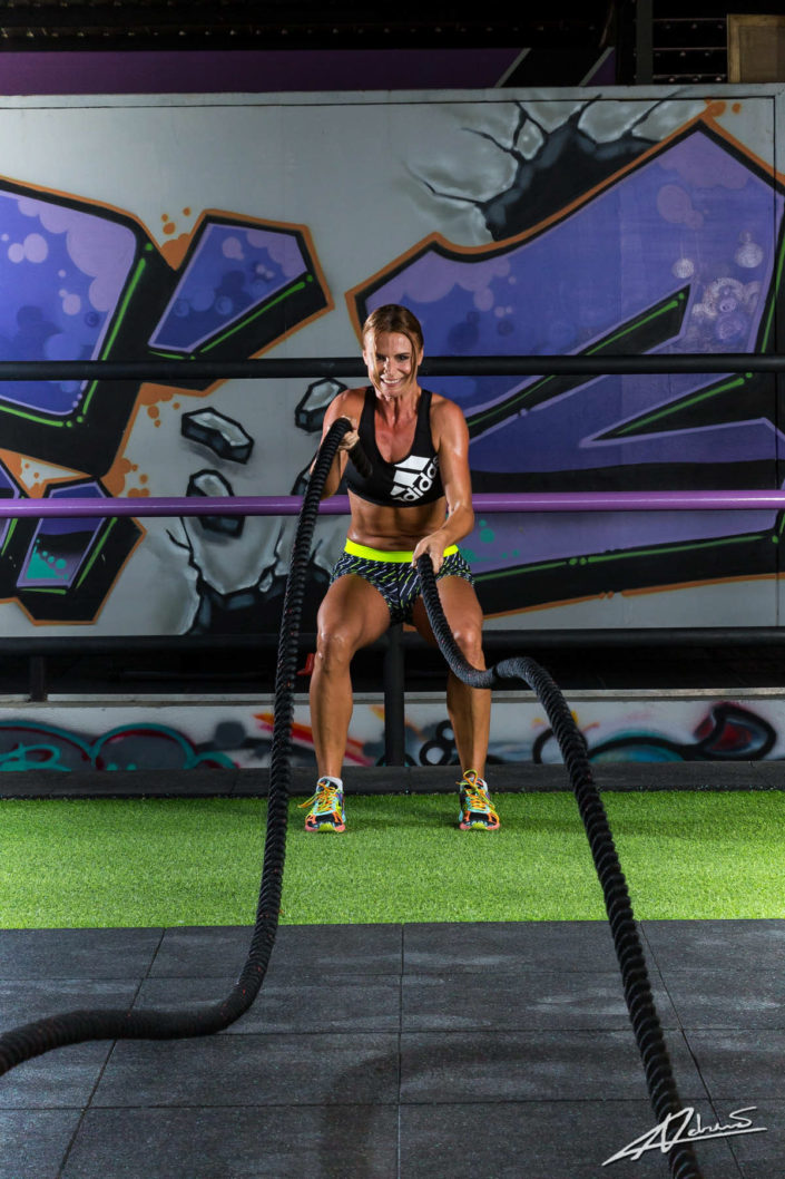 Fitness photography woman training with ropes.