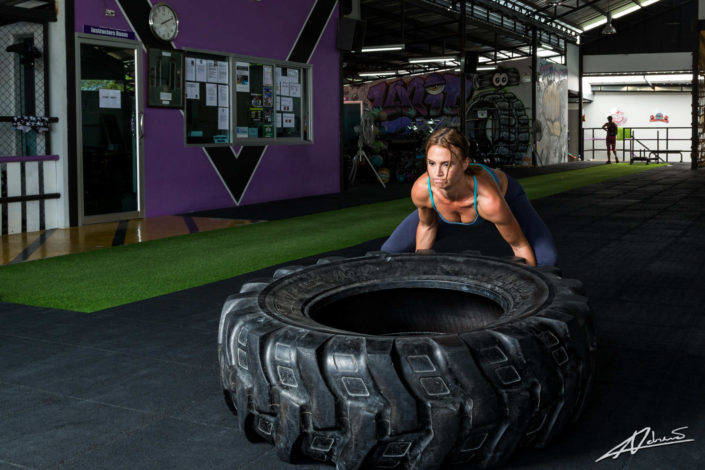 Fitness photography woman training with a tyre.
