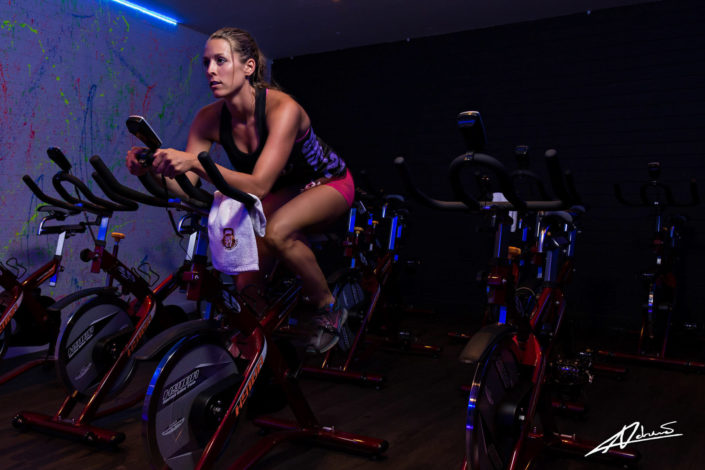 Fitness photography woman indoor cycling training.