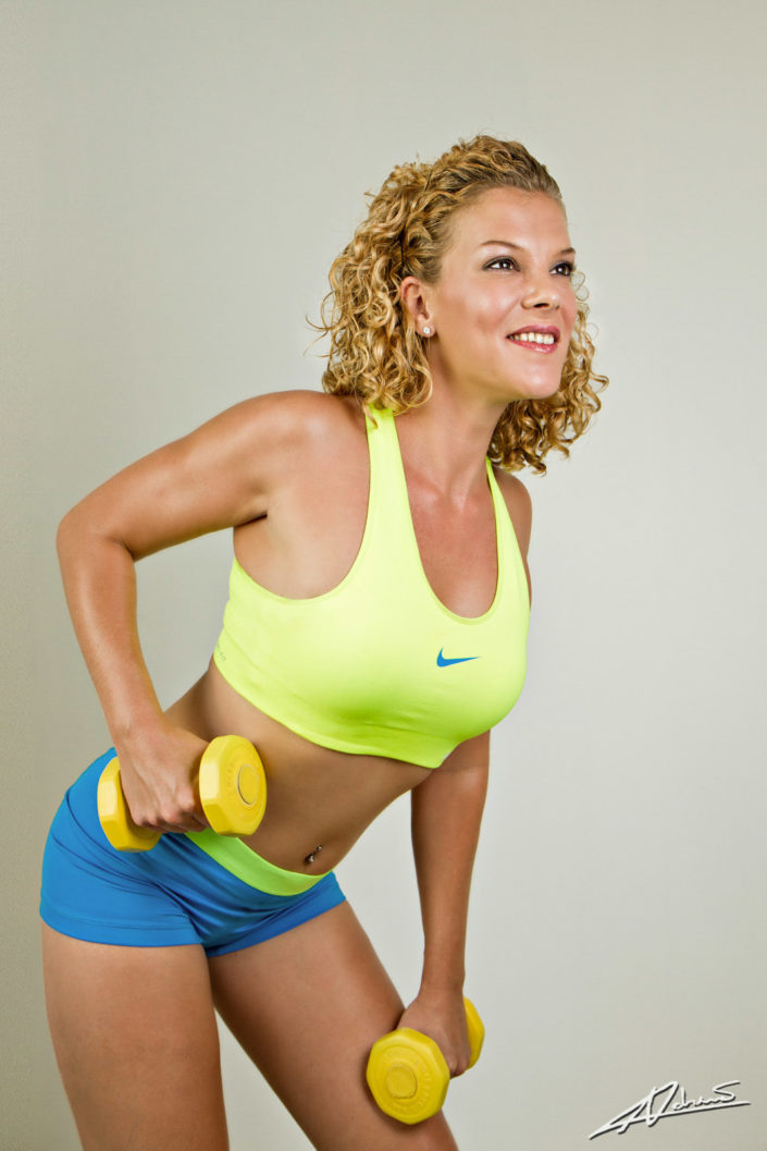 Fitness photography woman with dumbbells in the studio.