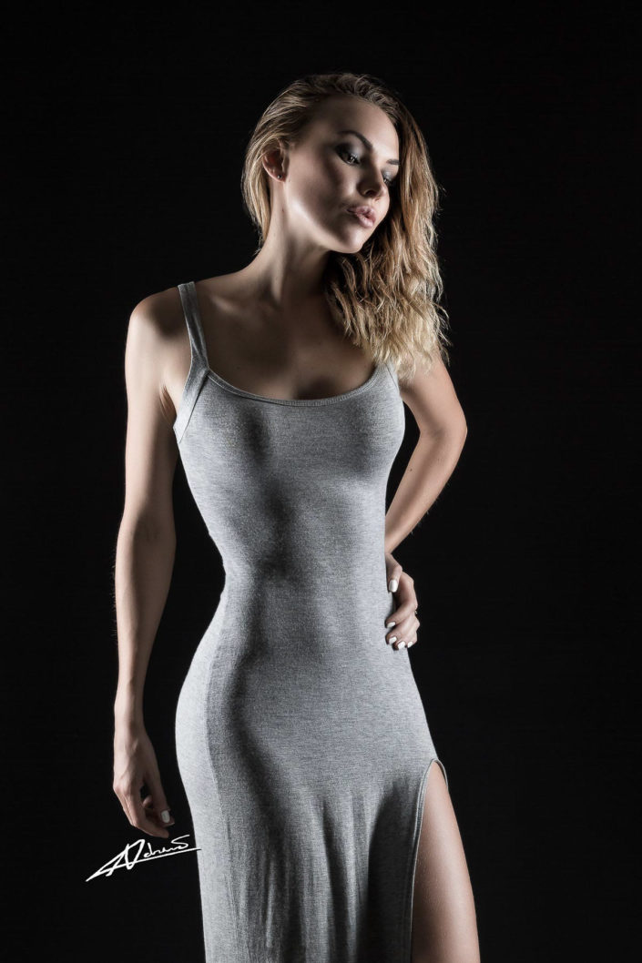 Model portfolio woman with grey dress in the studio.