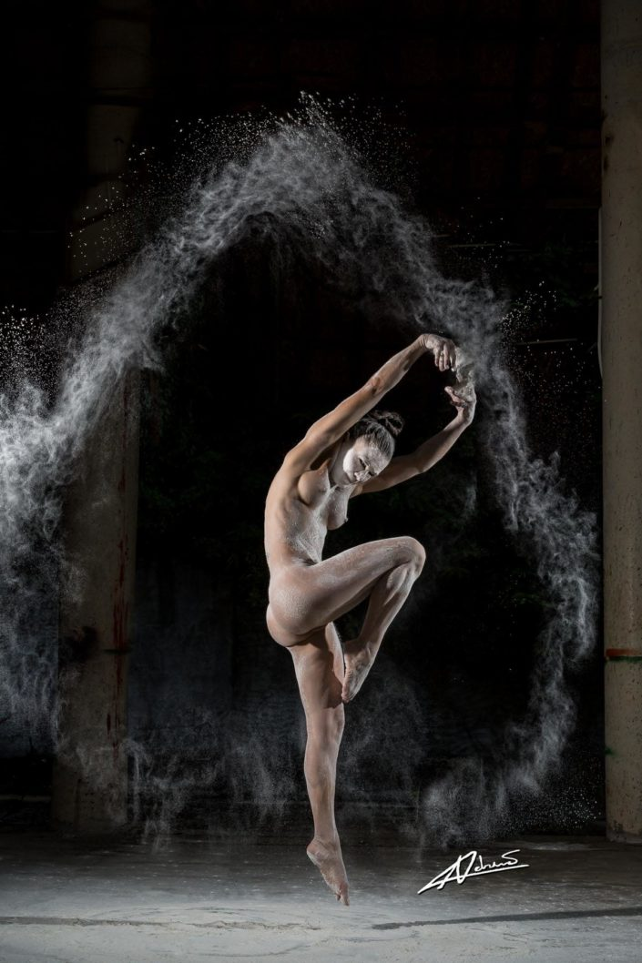 Nude photography woman jumping and throwing dust.
