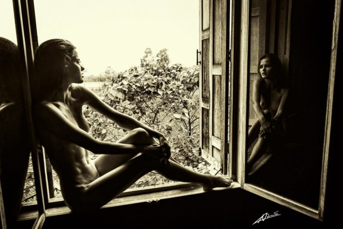 Nude photography woman sitting on the windows edge.