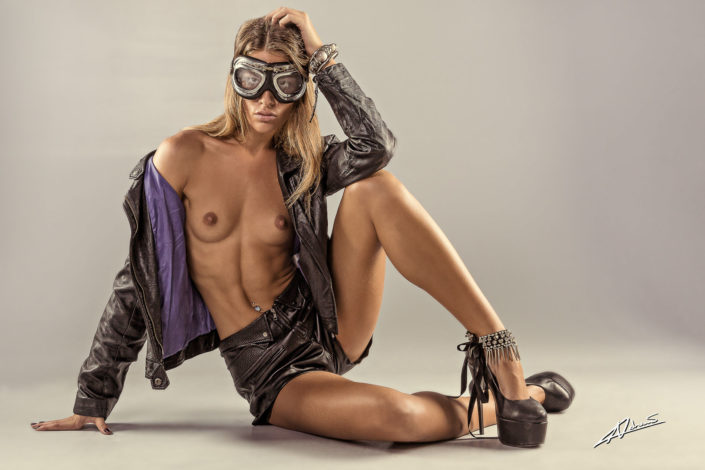 Nude photography woman with jacket and pilot goggles.
