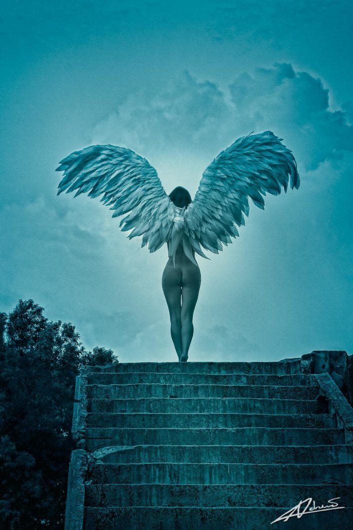 Nude photography woman with wings on top of the stairs.