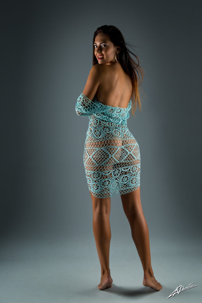 Nude photography womans back with net dress in the studio.