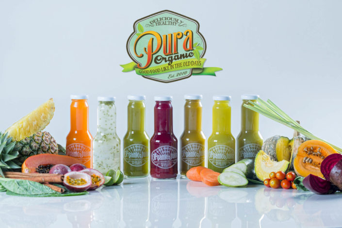 Product photography Pura organic juice bottles.
