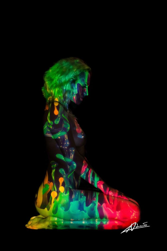 Projections-nude photography woman sitting side with colorfull picture.