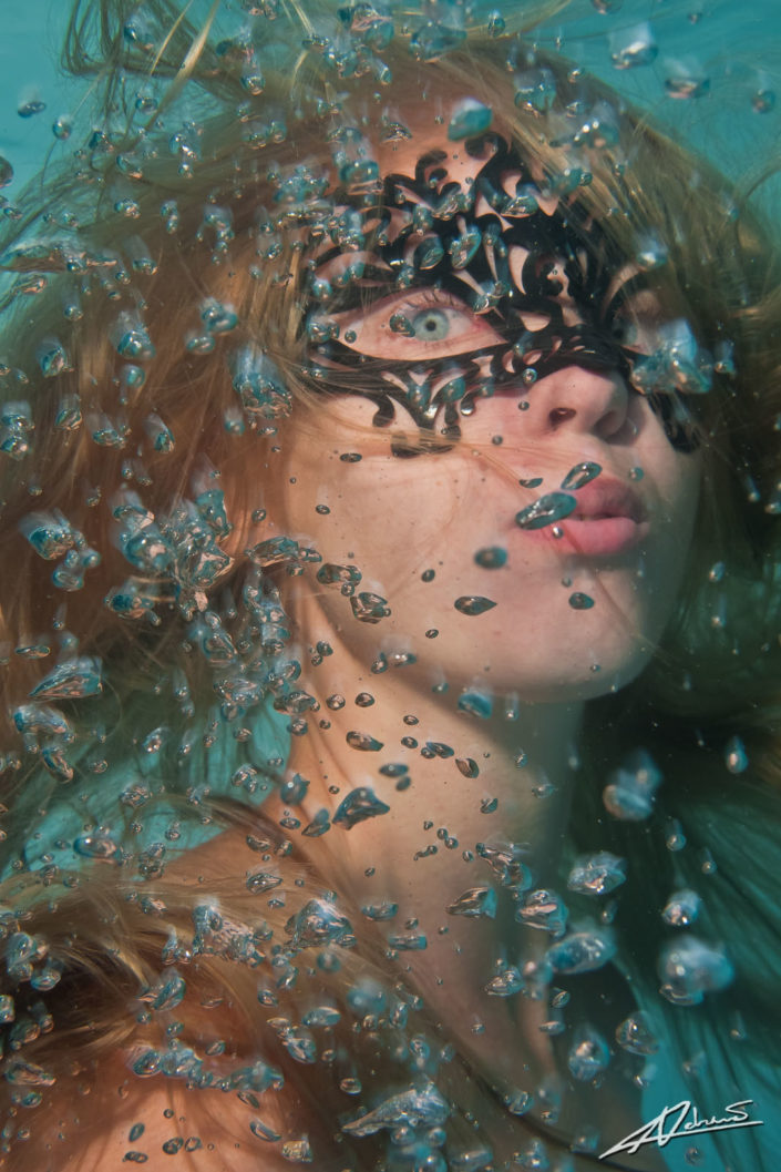 Underwater portrait woman with mask and bubbles.