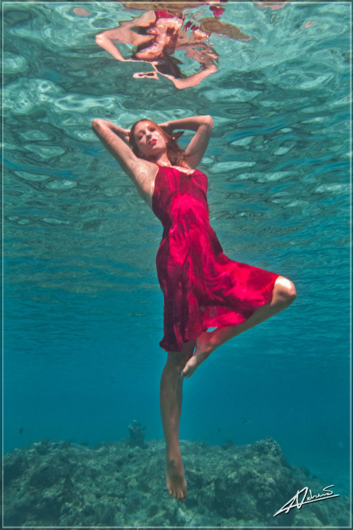 Underwater portrait woman with red dress.
