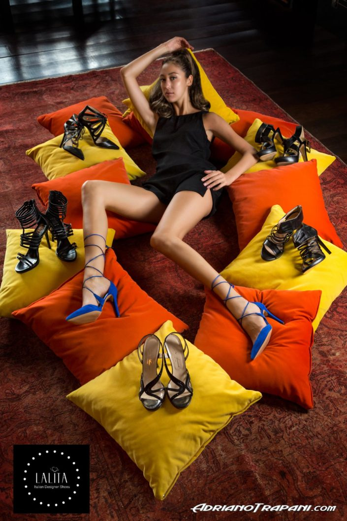 Fashion photography Lalita shoes model liying on pillows with shoes.