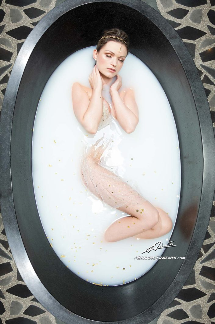 Fantasy photography woman in the bathtub with gold.
