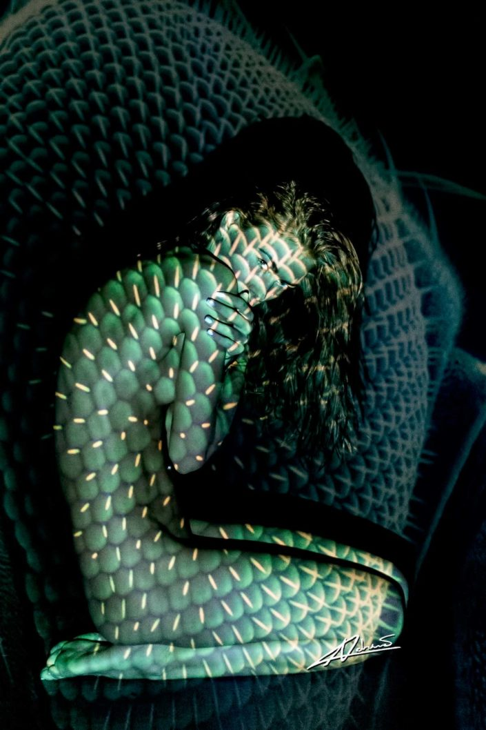 Projections woman sitting with snake skin picture.