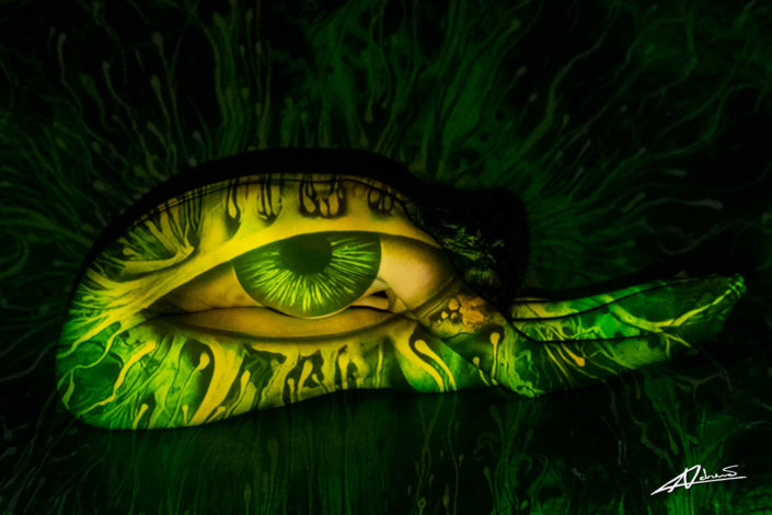 Projections-nude photography woman folded in yoga pose with green eye pattern.
