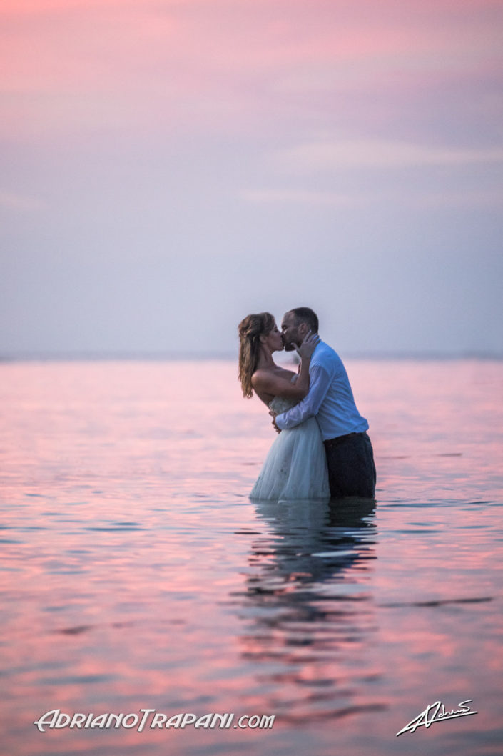 Wedding photography bride an groom romantic kiss in the ocean at sunset.