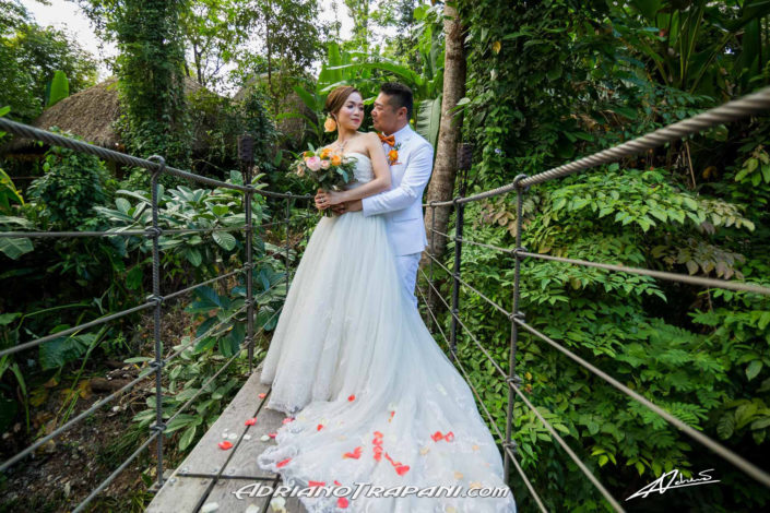 Wedding photography bride and groom hugging on suspension bridge.