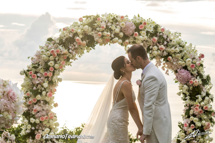 Wedding photography bride and groom kiss by the flower arch.