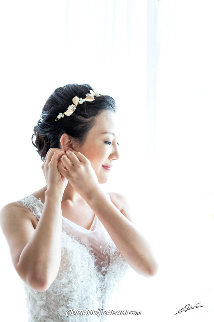 Wedding photography bride by the window putting earring on.
