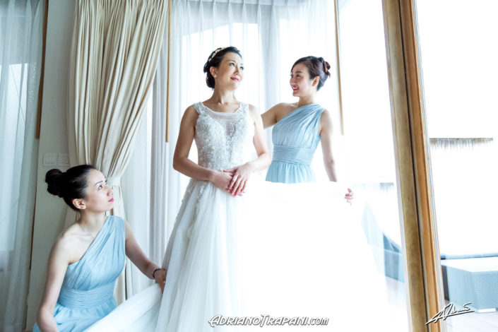 Wedding photography bridesmainds helping bride with bridal dress.
